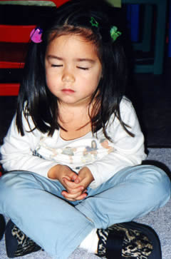 "A child during ""quiet time"" at an Ananda Marga school"